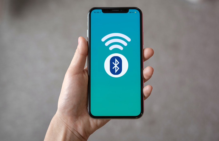 phone in hand with bluetooth icon