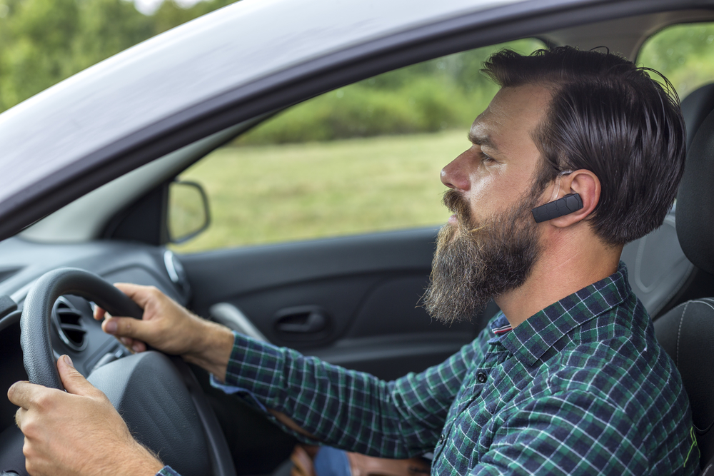 Man's Driving Wearing the Waterproof Bluetooth Earpiece