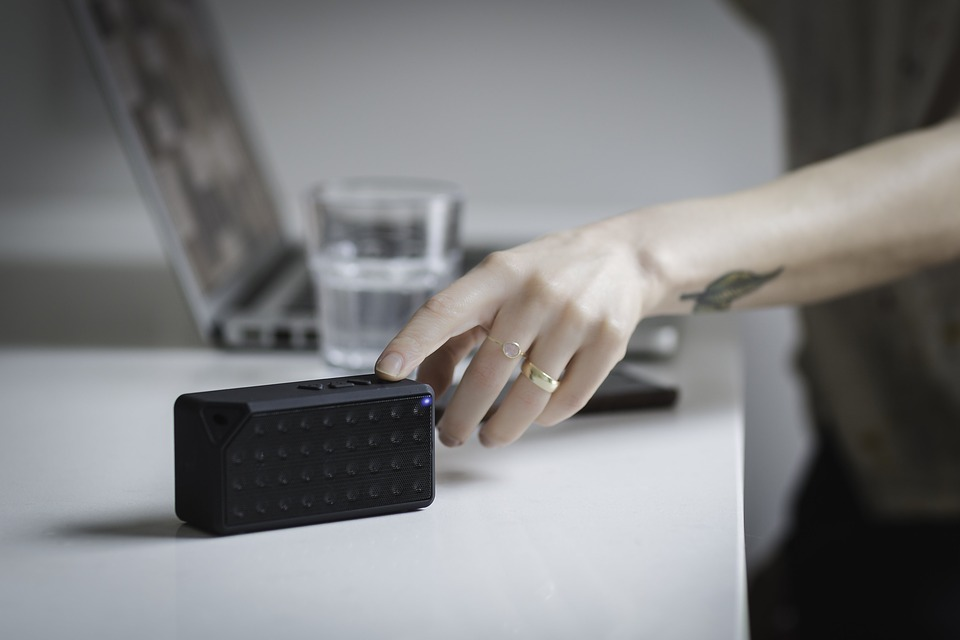 person pressing bluetooth speaker button
