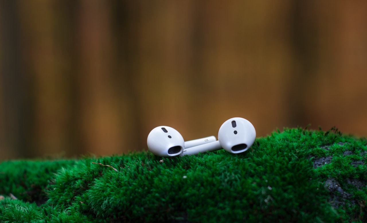 White airpods on greeen surface