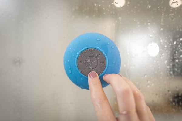 person pointing on bluetooth waterproof speaker